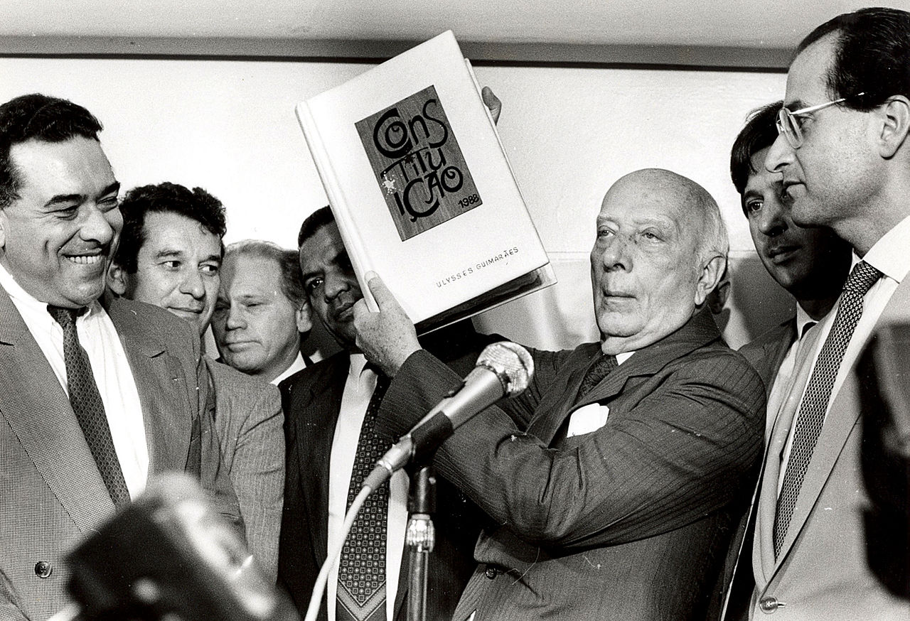 "A group of men stand behind a micrphone. One holds up a book with the word ""Constitution"" in portuguese on the front cover."